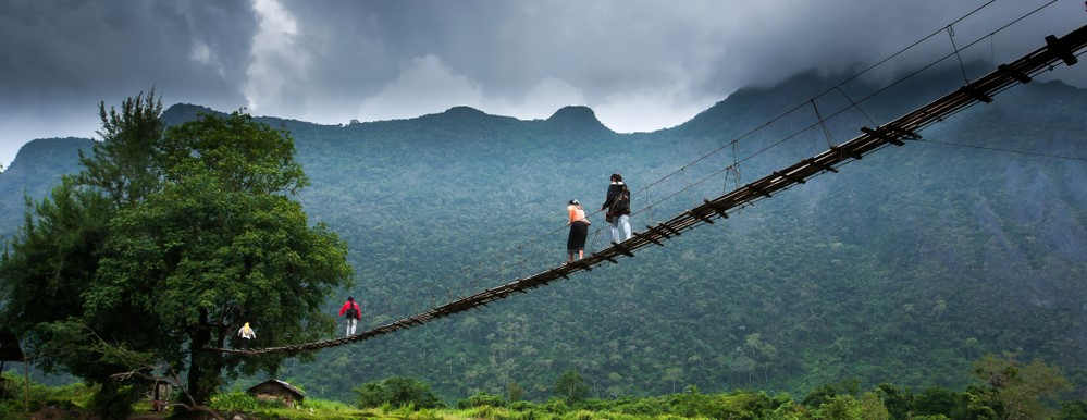 Shutterstock. A group of Laotian high school girls across a suspension footbridge over the Nam Song River, in North Lao PDR.