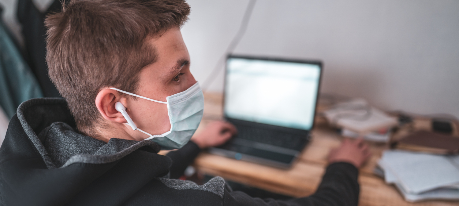 Teen boy in face mask with laptop homework during a coronavirus quarantine